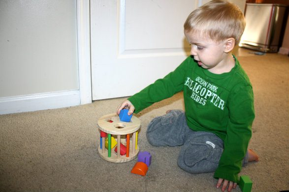 Playing Stacking Ring On Sand For Children